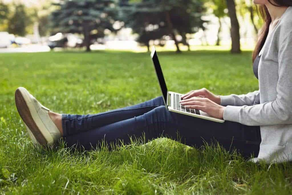 young pensive woman using laptop in park PL35JWE 1